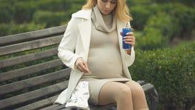 Blonde zwangere dame die spaanders in park, ongezonde kostsnack, ongezonde voeding eten stock footage