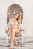Blonde zwangere vrouw in wit ondergoed binnen op stoel Royalty-vrije Stock Foto