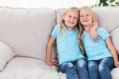 Blonde Zwillinge, die auf einer Couch sitzen Stockbilder