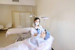 Blondecosmetologist die het tatoeëren van wenkbrauwen voor jonge vrouw bij kabinet maken Stock Foto