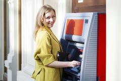 Blondedame die een geautomatiseerde tellermachine met behulp van stock afbeelding