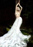 Blondeengel in lange witte rok die zich in donker bos bevinden Stock Afbeeldingen