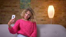 Blondehuisvrouw die in roze sweater mooie selfies op smartphone in comfortabele huisatmosfeer maken stock video
