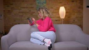 Blondehuisvrouw in roze sweaterzitting op bank die in tablet surfen en emotioneel in comfortabele huisatmosfeer reageren stock footage