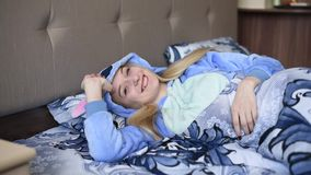 Blondemeisje in bed in de ochtend in blauwe pyjama's stock videobeelden