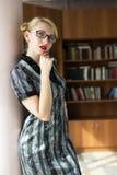 Blondemeisje in bibliotheek Stock Foto's