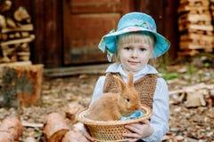 Blondemeisje in de hoed die een konijn houden stock fotografie