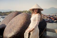 blondemeisje in de Vietnamese hoed van kledingsaanrakingen door barrière Royalty-vrije Stock Foto