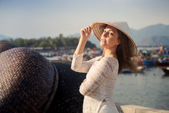 blondemeisje in de Vietnamese hoed van kledingsaanrakingen door barrière Stock Foto's