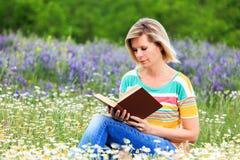 Blondemeisje die de bloemrijke weide lezen Stock Afbeelding