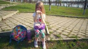 Blondemeisje die haar lunch in park op zonnige dag eten stock footage