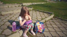 Blondemeisje die haar lunch in park op zonnige dag eten stock video