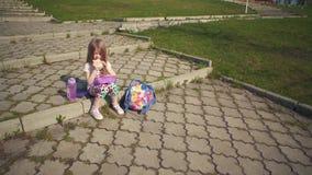 Blondemeisje die haar lunch in park op zonnige dag eten stock videobeelden