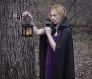 Blondemeisje die mantel dragen en lantaarn in het bos houden Royalty-vrije Stock Fotografie
