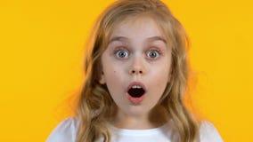 Blondemeisje die uiterst geschokt het horen nieuws, ge?soleerde gele achtergrond kijken stock video
