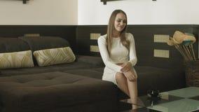Blondemeisje in een hotelruimte het drinken koffie stock footage