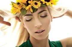 Blondemeisje in een kroon van gele bloemen Stock Foto's