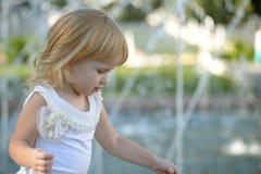 Blondemeisje in een park dichtbij de fontein royalty-vrije stock foto's
