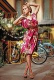Blondemeisje in een roze kleding met bloemen Royalty-vrije Stock Foto