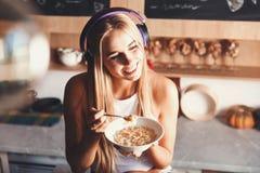 Blondemeisje het Luisteren Muziek en het Eten van Ontbijt stock fotografie