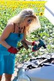 Blondemeisje met hulpmiddelen over open bonnet Grappig blonde die de machine met een hamer en schroevedraaiers proberen te herste stock afbeelding