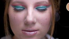 Blondemeisje met multicoloured samenstelling die zich langzaam en op met geheimzinnigheid in camera op vage lichtenachtergrond be stock videobeelden