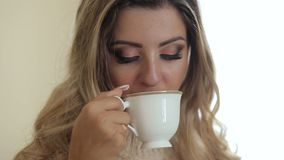 Blondemeisje met samenstelling het drinken thee, close-up stock video