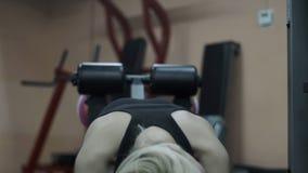 Blondemeisje opleiding bij de gymnastiek Vrouw belast met geschiktheid stock video