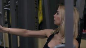 Blondemeisje opleiding bij de gymnastiek Vrouw belast met geschiktheid stock videobeelden