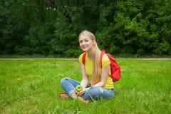 Blondemeisje uit in de openlucht dragende jeans en de zak Royalty-vrije Stock Fotografie
