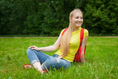 Blondemeisje uit in de openlucht dragende jeans en de zak Stock Foto