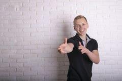 Blondemens die voorzijde richten tegen bakstenen muur royalty-vrije stock foto's
