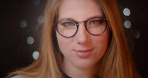 Blondemodel met heldere samenstelling in oogglazen die positief in camera op bokehachtergrond glimlachen stock footage