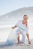 Blonder Aktivist, der Abfall auf dem Strand aufhebt Stockbild