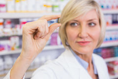 Blonder Apotheker in den Laborkitteln, die Pille zeigen Stockfoto