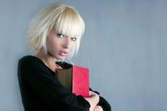 Blonder Art und Weisekursteilnehmer, der rotes Buch anhält Lizenzfreies Stockbild