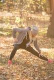 Blonder Athlet, der Beine aufwärmt und ausdehnt, bevor heraus laufen Lizenzfreie Stockfotografie
