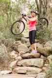 Blonder Athlet, der ihre Mountainbike über Felsen trägt Stockbild
