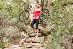 Blonder Athlet, der ihre Mountainbike über Felsen trägt Stockbilder