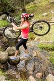 Blonder Athlet, der ihre Mountainbike über Strom trägt Stockfoto
