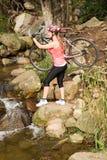 Blonder Athlet, der ihre Mountainbike über Strom trägt Lizenzfreies Stockfoto