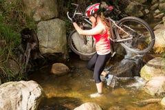 Blonder Athlet, der ihre Mountainbike über Strom trägt Lizenzfreie Stockbilder