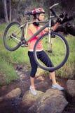 Blonder Athlet, der ihre Mountainbike über Strom trägt Stockfotografie