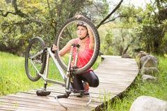 Blonder Athlet, der ihre Mountainbike überprüft Lizenzfreie Stockfotografie