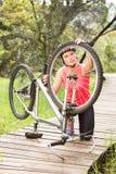 Blonder Athlet, der ihre Mountainbike überprüft Lizenzfreie Stockbilder