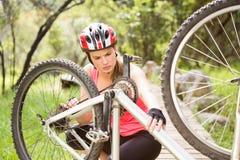 Blonder Athlet, der ihre Mountainbike überprüft Stockfotografie