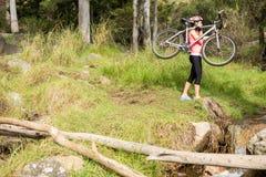 Blonder Athlet, der ihre Mountainbike trägt Stockbild