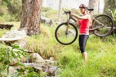 Blonder Athlet, der ihre Mountainbike trägt Lizenzfreie Stockfotografie