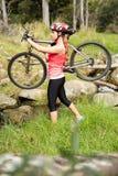 Blonder Athlet, der ihre Mountainbike trägt Lizenzfreies Stockfoto