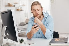 Blonder bärtiger männlicher Freiberufler installiert neue APP am intelligenten Telefon, herunterlädt Programm über Computer, benu Stockbilder